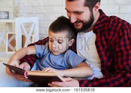Close-up of father and son sitting in an armchair together. Father and son reading an interesting book. Father holding a book while son looking attentively at the page