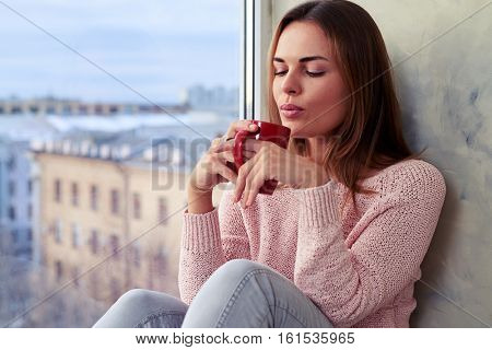 Close-up of beautiful girl with a cup of tea. Relaxing on the windowsill and blowing on it to cool. Wearing pullover and jeans