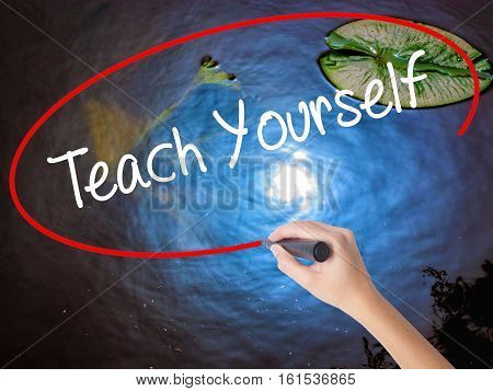 Woman Hand Writing Teach Yourself  With Marker Over Transparent Board