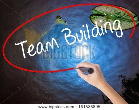 Woman Hand Writing Team Building With Marker Over Transparent Board