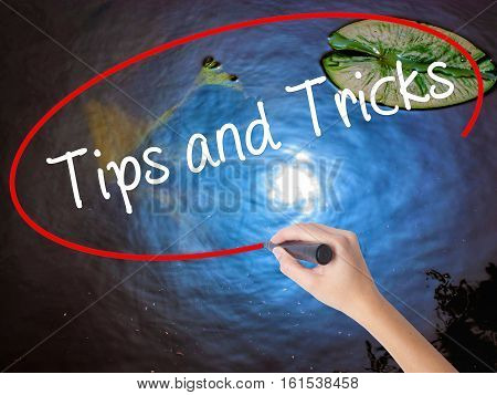 Woman Hand Writing Tips And Tricks With Marker Over Transparent Board