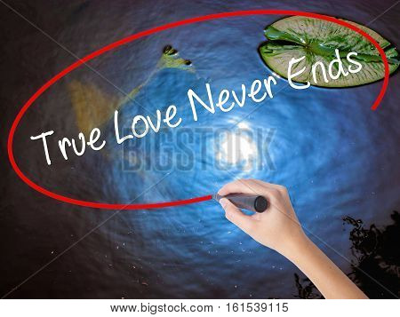 Woman Hand Writing True Love Never Ends With Marker Over Transparent Board