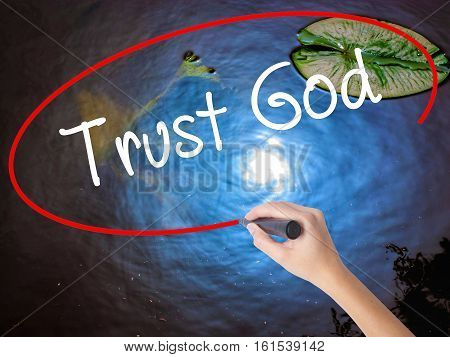 Woman Hand Writing Trust God  With Marker Over Transparent Board