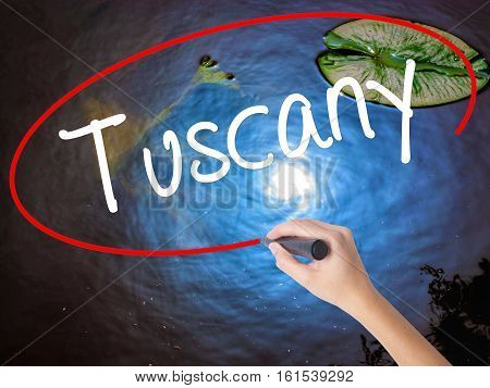 Woman Hand Writing Tuscany With Marker Over Transparent Board.
