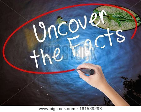Woman Hand Writing Uncover The Facts With Marker Over Transparent Board