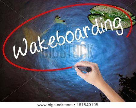 Woman Hand Writing Wakeboarding With Marker Over Transparent Board.