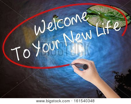 Woman Hand Writing Welcome To Your New Life With Marker Over Transparent Board