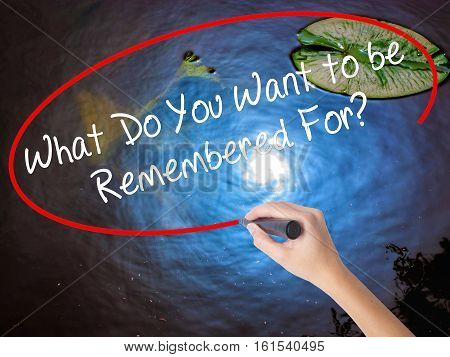 Woman Hand Writing What Do You Want To Be Remembered For? With Marker Over Transparent Board