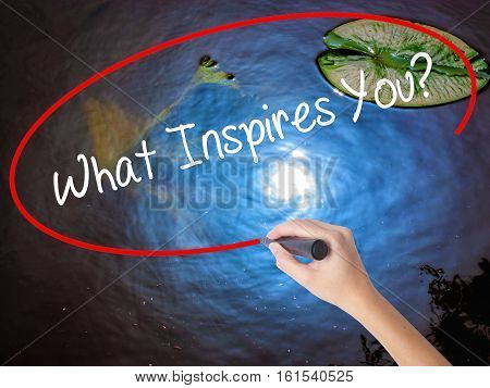 Woman Hand Writing What Inspires You? With Marker Over Transparent Board