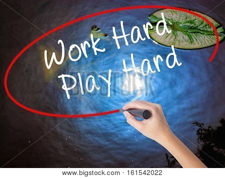 Woman Hand Writing Work Hard Play Hard  With Marker Over Transparent Board