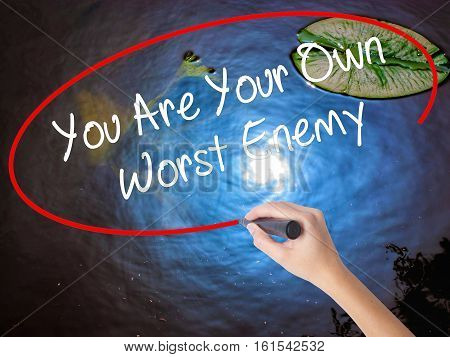 Woman Hand Writing You Are Your Own Worst Enemy With Marker Over Transparent Board