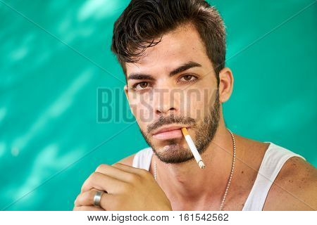 Real Cuban people and emotions portrait of young hispanic man from Havana Cuba looking at camera with serious expression smoking cigarette and blowing smoke