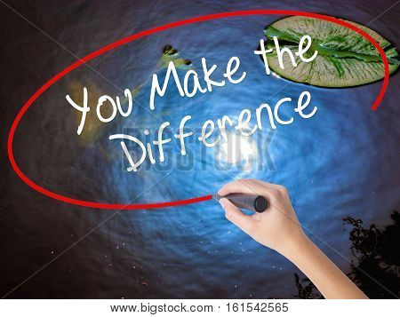 Woman Hand Writing You Make The Difference With Marker Over Transparent Board