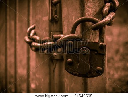 The Old And Rusty Lock On A Metal Gate.