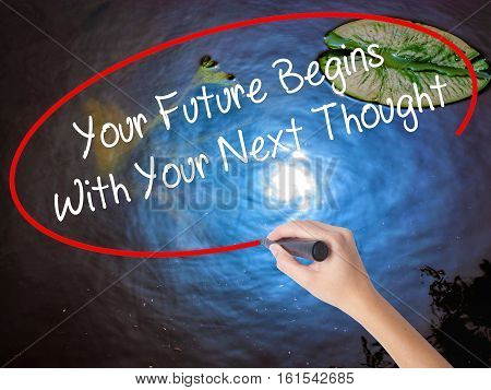 Woman Hand Writing Your Future Begins With Your Next Thought With Marker Over Transparent Board.