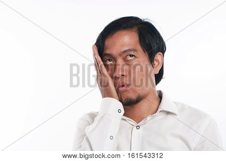 Photo image portrait of a funny young Asian businessman wearing glasses looked very bored close up portrait showing tired face with one hands pressing his cheek gesture