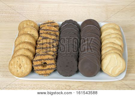 ALAMEDA CA - FEBRUARY 09 2016: White rectangular plate with the five most popular original Girl Scout created by ABC Bakers. Available annually during Girl Scout cookie sales. on light wood table