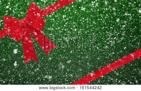 Large red Christmas bow isolate on green glitter bokeh background with snowfall effect