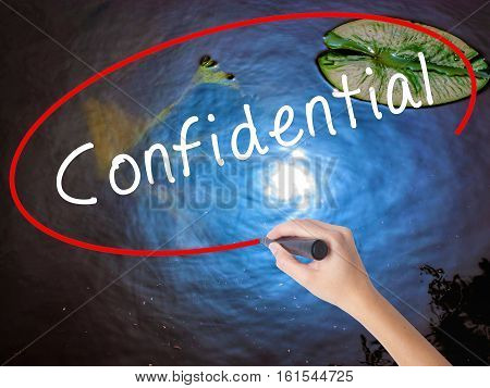 Woman Hand Writing Confidential With Marker Over Transparent Board