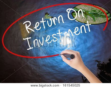 Woman Hand Writing Return On Investment  With Marker Over Transparent Board