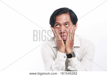 Photo image portrait of a funny young Asian businessman wearing glasses looked very bored close up portrait showing tired face with both hands pressing his cheeks gesture