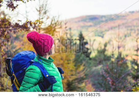 Hiking woman with backpack looking at inspirational autumn mountains. Fitness travel and healthy lifestyle outdoors in fall season nature. Female backpacker tourist walking and looking around.