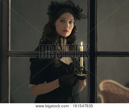 Retro Victorian Woman In Black Dress Standing Behind Window Holding Candlestick.