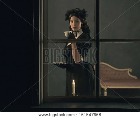 Vintage Victorian Girl Drinking Cup Of Tea Behind Window.