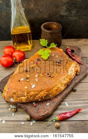 Marinated steak with spices on a wooden table. Top view