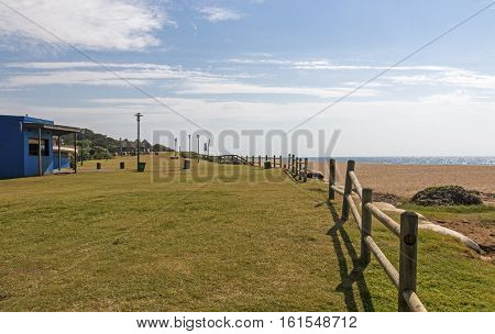 Sunshades And Wooden Barrier In Grass Recreational Area