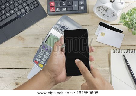 Cashier Men Hand Holding Telephone Credit Card Terminal Or Edc On Cashier Wooden Table In The Store