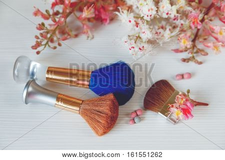 There White and Pink Branches of Chestnut Tree,Two Make Up Brown and One Blue Brushes are on White Table.Selective Focus