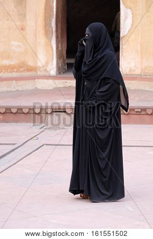 AGRA, INDIA - FEBRUARY 14 : Muslim woman talking on a mobile phone in Red Fort, Agra. Uttar Pradesh, India on February 14, 2016.