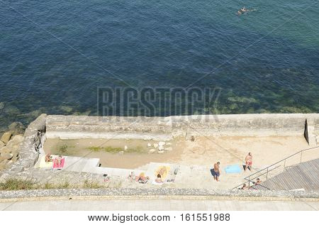 BAYONA, SPAIN - AUGUST 7, 2016: People having sun at stone terrace next to the sea in Bayona Galicia Spain.