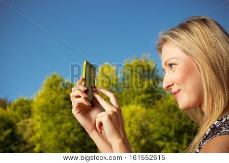 Woman Sitting In Park, Using Phone Taking Pictures