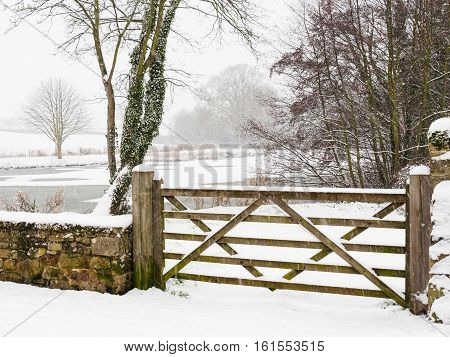 Winter scene with gate and settled and falling snow by Melbourne Pool Melbourne Derbyshire England.