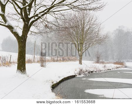 Winter scene with settled and falling snow by Melbourne Pool Melbourne Derbyshire England.