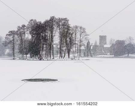 Winter scene with settled and falling snow by Melbourne Pool Melbourne Derbyshire England looking towards the parish church.