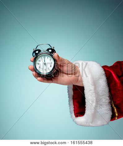 Santa holding an old alarm clock on blue background
