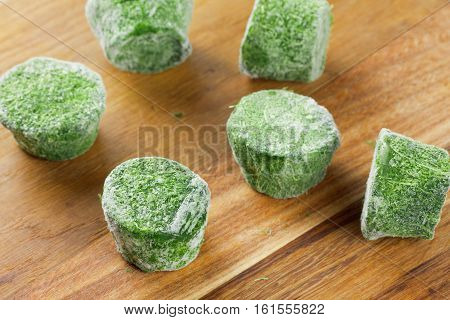 Group of frozen spinach briquette blocks on wooden background