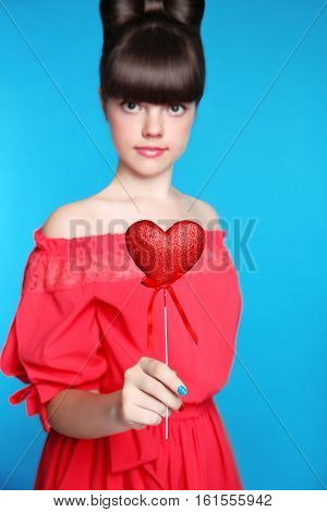 Red Heart In Teen Girl Hand. Brunette Young Model  With Bow Hair Style,  Isolated In Blue Background