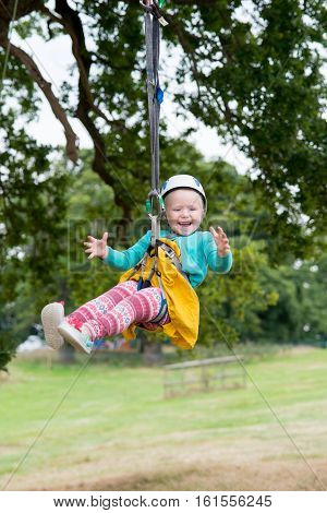 Laughing Blonde Child In Helmet Hangs From Zip Line