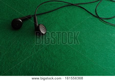 A set of earphones isolated against a green background