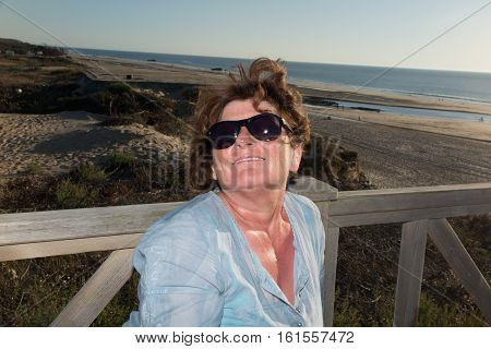 senior woman during vacation near the sand beach on summer with black glasses