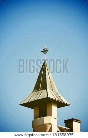 Cross on top of the church against blue sky and vignette