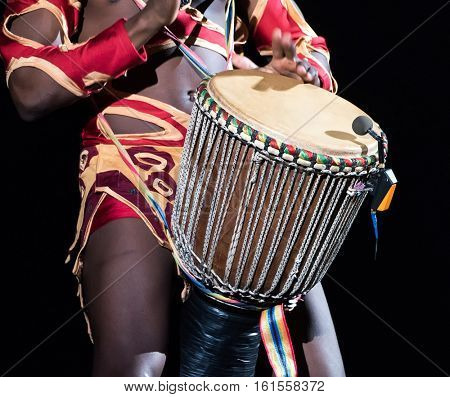 Detail of african drummer beating the drum