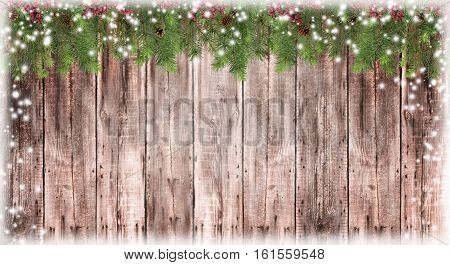 Wooden Blurred christmas background. Branches of trees cones red berries. snow on the old boards. Christmas atmosphere. Card. New Year. Snowfall.