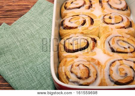 Rolls of puff pastry with cinnamon on wooden table
