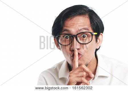 Photo image portrait of a funny young Asian businessman wearing glasses showing ssh sign close up portrait with one finger on lips asking to silence gesture over white background