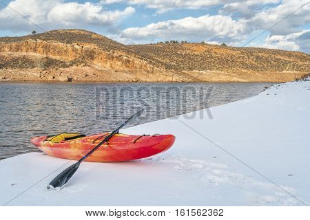 winter kayaking in Colorado - red whitewater kayak on shore of Horsetooth Reservoir near Fort Collins